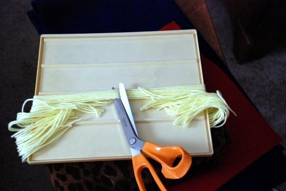 Переверните картон и разрежьте волосы по центру
