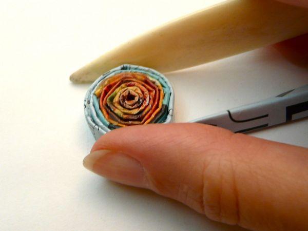 """Используйте переплетную косточку или нож, чтобы выравнять уровни каждого оборота или """"размять"""" бумагу, чтобы при скручивании она ложилась без углов"""